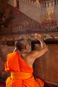 Monk retouching a temple mural, Bangkok.