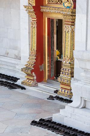 Orderly shoes outside temple entrance, Bangkok.