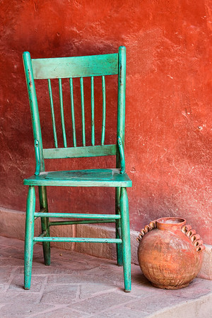 Empty chair and pottery on porch in Mexico.
