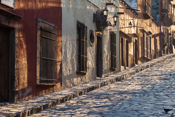 Mexico, San Miguel de Allende. Sunlight streams down a cobblestone lane in the village.