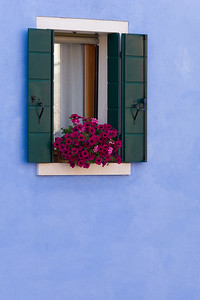 Italy, Venice. Colorful windows with flower boxes on Burano Island.