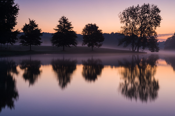 Mist rises over lake at dawn.