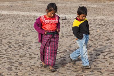 Young Guatemalan boy and girl walking through square.