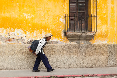 Man walking past yellow wall, Guatemala.