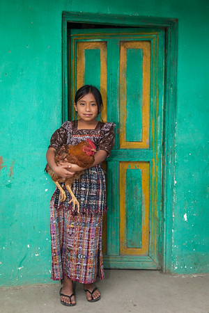 Guatemalan girl holding rooster.