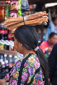 Guatemala woman carries kindling on her head.