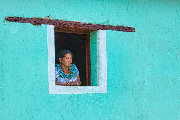 Woman at the window of her house.