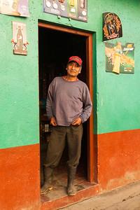 Man standing in doorway of shop in Santa Maria de Jesus.
