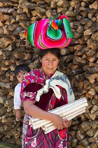 Woman with head bundle and child on her back, San Juan La Laguna.