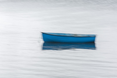 Ireland, Portmagee. A blue dinghy bobs in the harbor, creating an abstract impression.