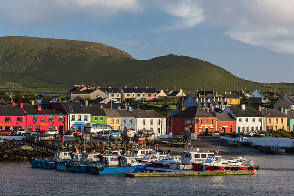 Sunlight illuminates the village of Portmagee, Ireland.