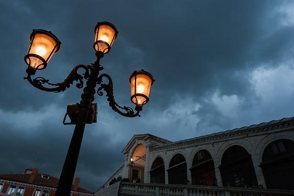 Stormy skies, lamppost and Rialto Bridge, Venice.