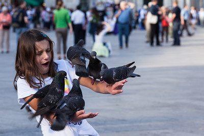 Pigeons on girl's arms, Venice, Italy.