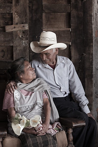 Elderly mexican couple smiling at each other.