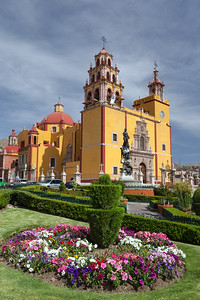 Mexico, Guanajuato.  Gardens welcome visitors to the colorful town of Guanajato. The Basílica of our Lady of Guanajuato is in the background.