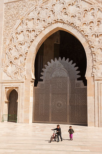 Children play below towering walls of mosque, Casablanca, Morocco.