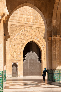 King Hassan II mosque dwarfs a woman standing beneath archway.