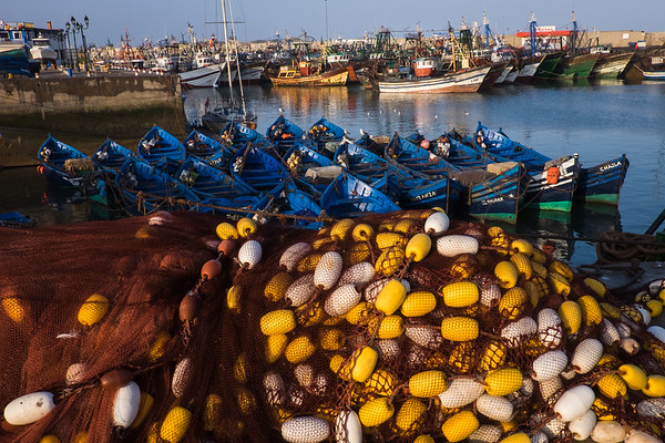 Africa, Morocco, Essouira. A view of the port with fishing nets, boats and commercial vessels.