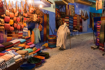 Africa, Morocco. An elderly man walks past tourist shops along a street in the blue city of Chefchaouen.