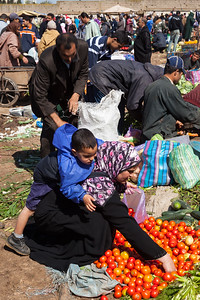 Woman buying tomatoes at market, Morocco.