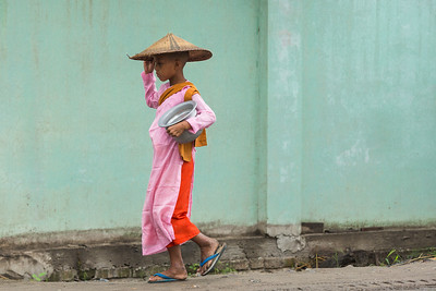 Nun walking with rice bowl, Mandalay, Myanmar.