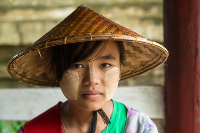 Young burmese girl with thanaka paste decoration on her face, Myanmar.