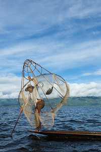 Fisherman with fish in net, Inle Lake, Myanmar.