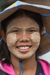 Smiling Burmese girl with Thanaka powder on her face.