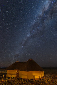 Thatched huts and Milky Way, Namibia.