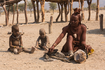 Himba mother prepares a meal, Namibia.