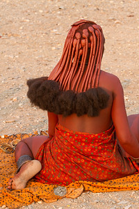 Africa, Namibia. A Himba woman dressed traditionally, and wearing hair extensions.