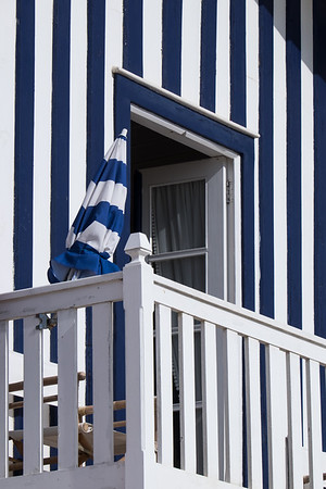 Blue-striped umbrella and house, Costa Nova, Portugal.