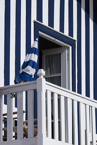 Blue-striped umbrella and house, Costa Nova, Portugal.