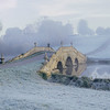 The Oxford Bridge in winter with thick frost covering the ground and mist in the air at Stowe Landscape Gardens, Buckinghamshire