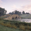 A view over the early morning mist looking towards the Oxford Bridge at Stowe Landscape Gardens, Buckinghamshire