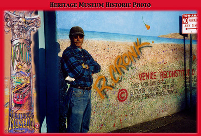 "PHOTO: Rip Cronk - The Man Who Painted Venice Rip is seen here with ""Venice Reconstituted"" which appears on the West wall of Danny's. Thanks to his amazing talents and a unique relationship with building owners like General Real Estate, Venice is graced with many signature images - a Van Gogh-like ""Homage to a Starry Knight"", the 5-story ""Abbot Kinney"" painted for the 2005 Centennial, and his world famous portrait of Jim Morrison, ""Morning Shot"", among others. His main tools? Airbrush and spider chair. Photo courtesy: www.VeniceHeritageMuseum.org. ""Envisioning a Venice History Museum"""