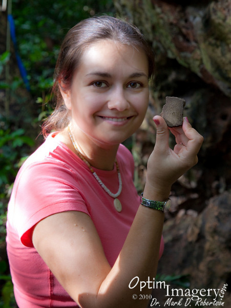 Olga is holding a piece of history.  This may have been part of a pottery vessel for an important Chamorro person.  Or, perhaps a person drank water from this vessel prior to conceiving progeny who gave rise to the modern Hocogs, or Naputis, or Manglonas, or .........<br /> <br /> A lot of things have happened in the last 1,000 years.  And this shard (or the vessel it broke off of) has probably been here all that time.