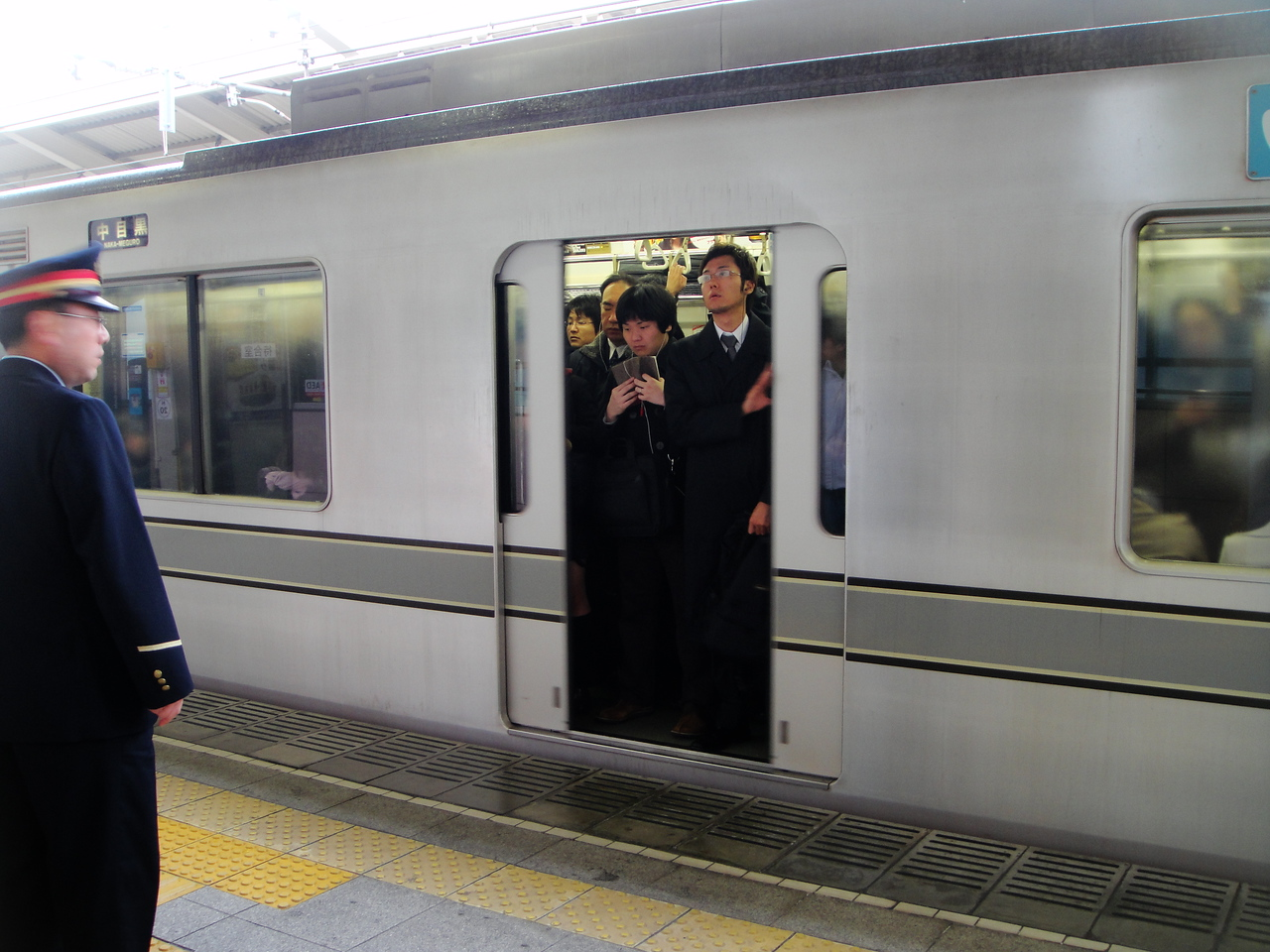 Yes, the gentleman on the left is there to assure that everyone can get inside...and he is happy to give a little push if everyone isn't properly tucked into the train.