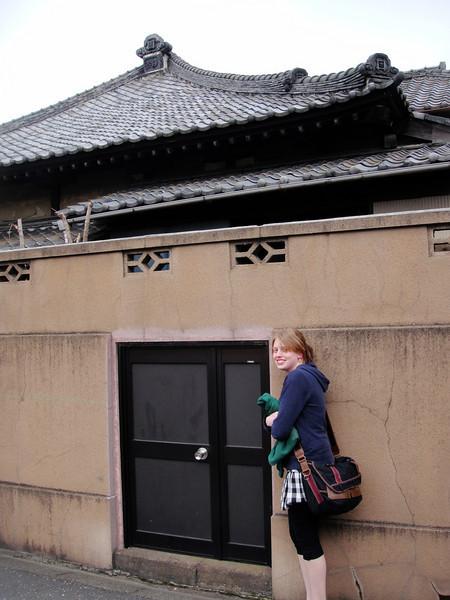Ashle feeling talk at an alleyway door.