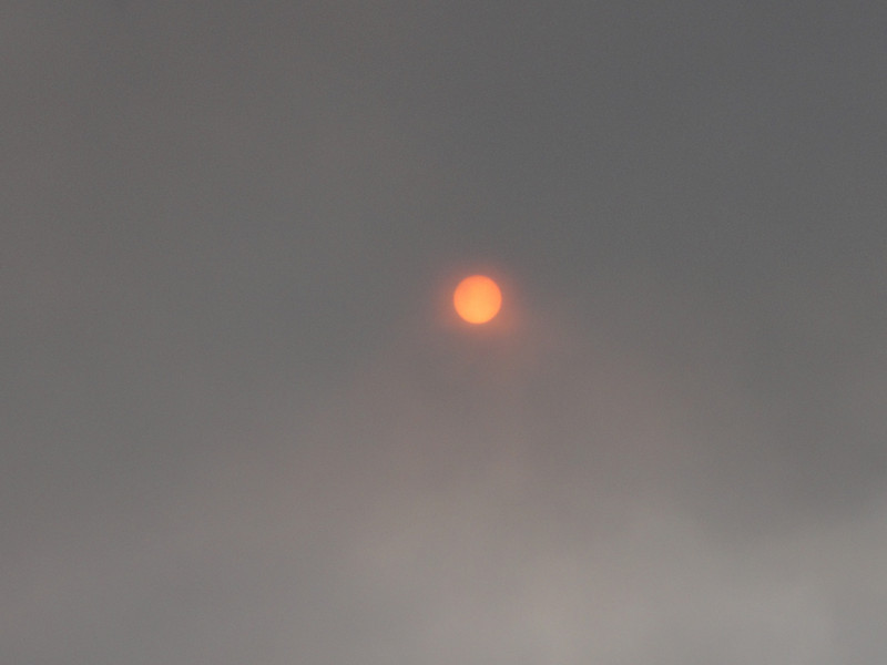 The steaming volcano was miles away, but the color of the sun made it evident we were in its path