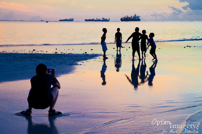 Local photographer getting the snap of local kids.  3 readiness ships in the distance.