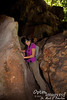 Kate squeezes through the little passageway for the trail to the catwalk at Kalabera Cave.