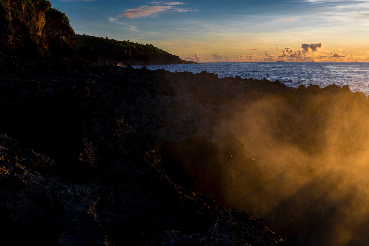 MIST FROM SPOUTING HORN CATCHES GOLDEN RAYS OF SUNSET