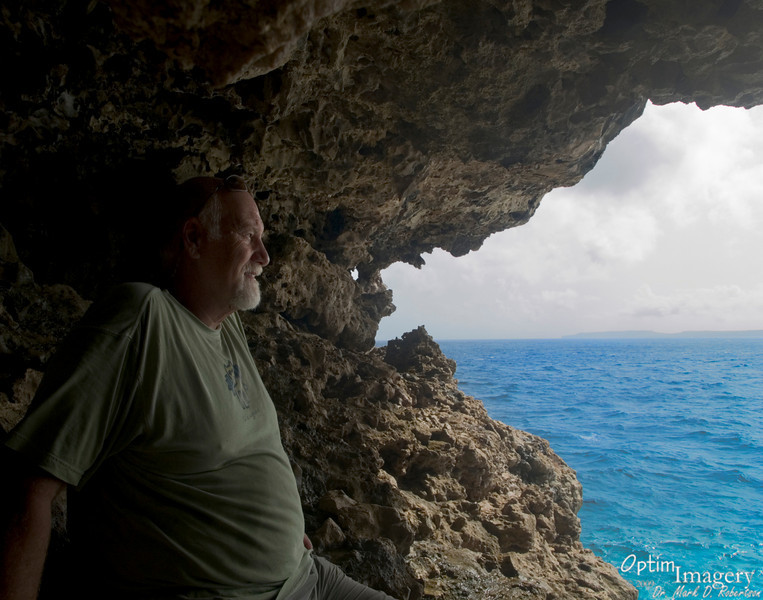 "Beneath the trail to the ""Toilet Bowl"" overlook is this cool cave, allowing for a spectacular view over the water toward Tinian (visible here in the distance)."