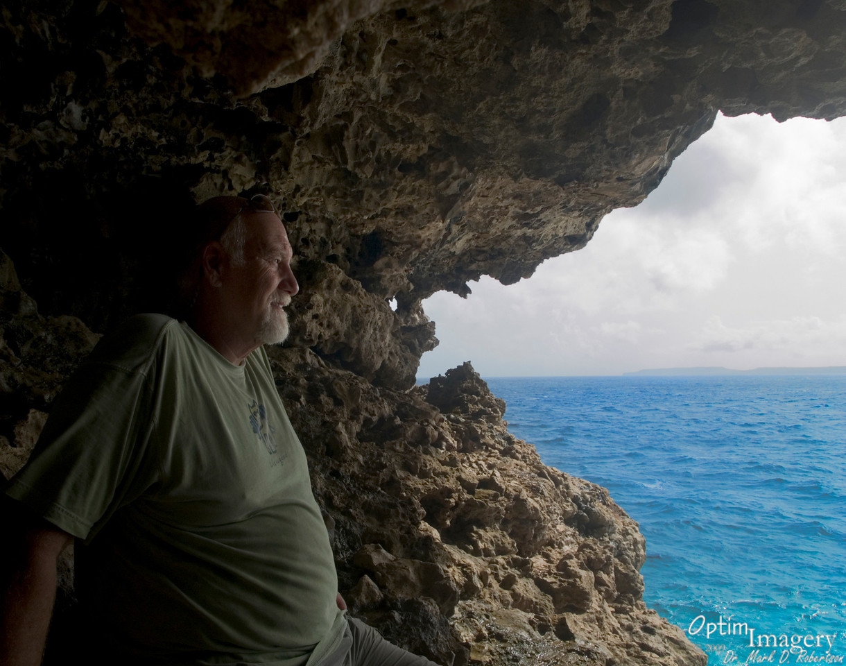 """Beneath the trail to the """"Toilet Bowl"""" overlook is this cool cave, allowing for a spectacular view over the water toward Tinian (visible here in the distance)."""