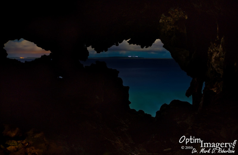 "Looking south, out the Naftan Cave, toward Tinian.  The yellow lights to the left are likely lights of a small village community (maybe Marpo Heights?).  The white lights to the right are on the Voice of America Broadcasting towers.<br /> <br /> The moon was behind me (which is why you have some illumination on the foreground walls).  This is a composite of 7 photos, ranging in exposure from 1 minute to 20 minutes, and combined in a way to enhance range of exposure (""dynamic range,"" to use the official terminology).  For those of you who are familiar with High Dynamic Range programs, I prefer to do it manually.<br /> <br /> To give you some idea of the dedication (idiocy?) required to do such night photography:  Consider that this one photograph probably required about 45 minutes or so of total exposure time for all the individual shots.  My camera has a noise-reduction feature which ""exposes"" the sensor (with the shutter closed) for an equal amount of time after the shot is taken (and then uses that information to cancel out some of the noise {""grain""} which is inherent in long and under-exposed photographs.  So, ignoring the time to get there and set up, this one picture you see required about 90 minutes of camera exposure time.  Of course, that is also ignoring the Photoshop time in combining the individual shots.<br /> <br /> But, it is a lot of fun, too!  Amazing how much color is there, if the exposure is long enough (I could not see any of this color that night, except for the yellow cast of the lights to the left)!"