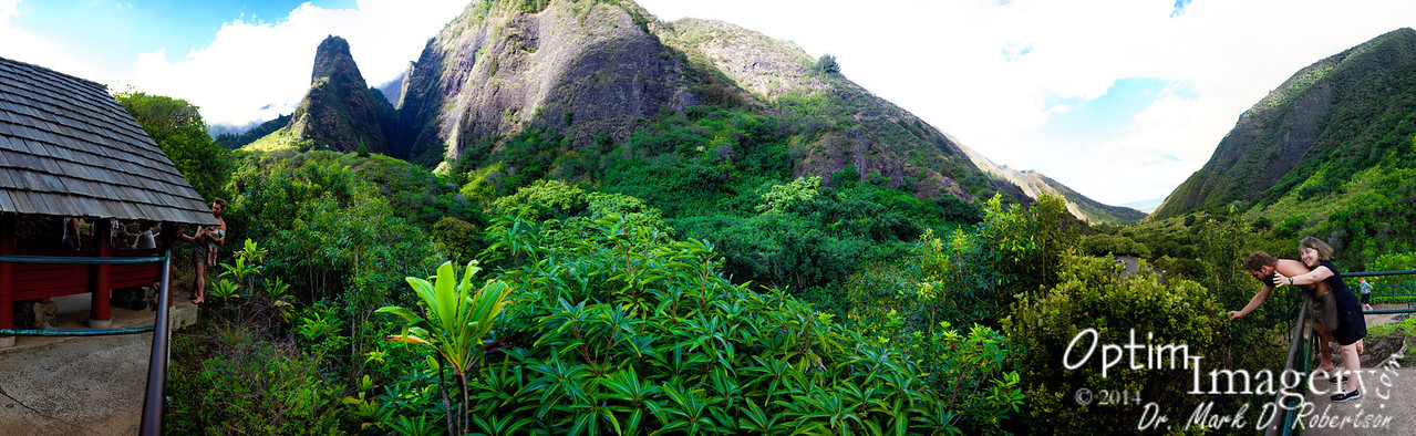 17-photo panorama entailing at least 180-degrees.  To your right you are looking down Iao Valley.  To your left you are looking up the same valley.  At 1,200 feet tall, Iao Needle is to obvious protuberance between the red pavilion and the hill with the top extending beyond the top of the photo.