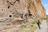 """Here you see more of the area where they built stone structures to add to their dwelling area. They also decorated the cliff.  You can see some of the petroglyphs.<br /> <br /> It's my understanding that the Tyuonyi (see photo 3) was not started until these canyon-wall dwellings / add-ons were pretty well saturated with people. It's also my understanding that it is NOT as though all the inhabitants moved from the cliffs to the valley floor. Rather, the Tyuonyi was sort of like a modern """"new addition"""" to the area, with some inhabitants still living along the cliffs at the same time as others moved to the Tyuonyi."""