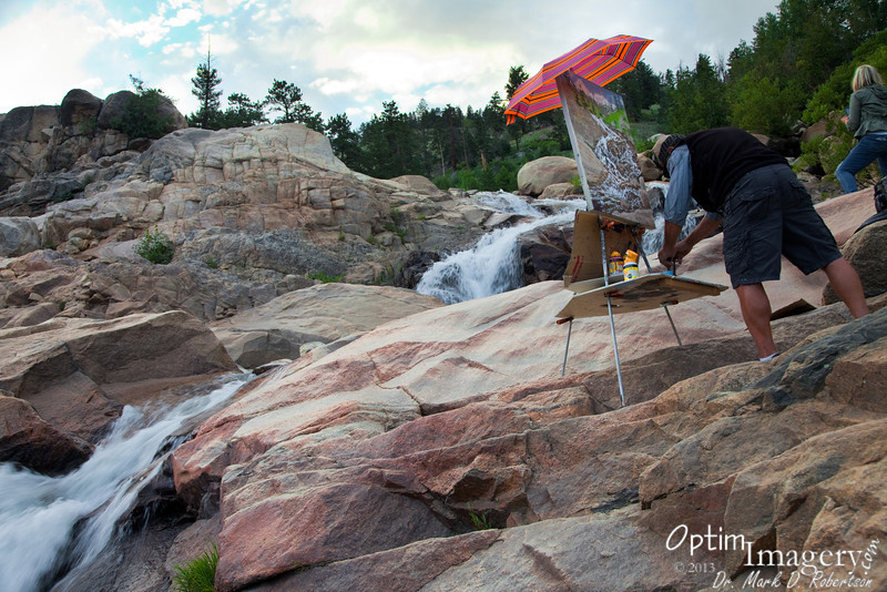 An artist paints the Roaring River waterfall just above the alluvial fan from the Lawn Lake flood.