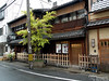 """These are traditional Machiya, or row houses. They usually house both a business and the owner's residence. Locals call them unagi no nedoko, which literally translates to """"bedrooms of eels."""" The term describes the dimensions and is not intended as an insult to the inhabitants: These buildings are often at least 10 times as long as they are wide. Taxes used to be levied based on frontage, so people built long and narrow to have sizeable buildings and very little road frontage. In the Edo period, people of nobility were starting to fear that the business class was becomming too powerful, so laws were passed prohibiting business owners from having more than 2 stories in their buildings. The second stories actually used to have closely spaced vertical wooden slats (instead of the glass you see here). The spaces between the boards were """"obviously"""" for ventilation (obvious to the visiting nobility), but in actuality, the design was to allow the business owner to watch from the second story without being seen. You see, in addition to the prohibition on the height of buildings, laws were also passed forbidding commoners from ever being above noble-men. The business owners wanted to be able to observe what was going on in the streets below. They had to make sure that they could see down without being seen. You'll see a better example of a Machiya with a traditional 2nd story in a moment."""